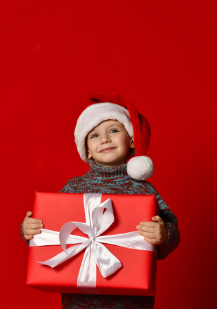 Funny smiling joyful  child boy in Santa red hat holding  big Christmas gift in hand over the red background Stock Photo
