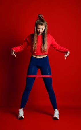 Woman with good physique doing stretching work out with elastic bands. Sports girl in fashionable sportswear on red background. points fingers to the tape