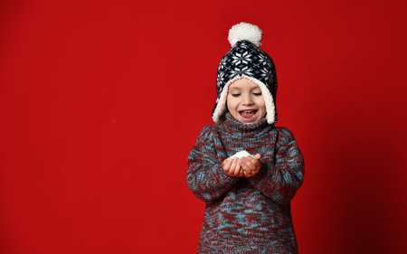 Little boy in a dark knitted hat with a pompon holds snow in his hands and happily enthusiastically looks at the camera in surprise