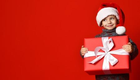 Niño divertido sonriente en Santa sombrero rojo con regalo de Navidad en la mano sobre fondo de pared roja. Concepto de Nochebuena.