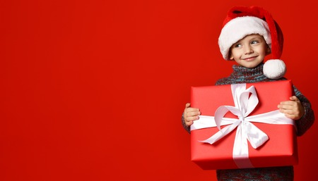 Smiling funny child in Santa red hat holding Christmas gift in hand over red wall background. Christmas eve concept. Stockfoto
