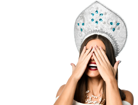 Young woman in kokoshnik cap covering her eyes with her hands smiling. Human positive emotions and feelings.