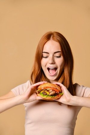 Funny crazy smiling Skinny ginger girl in beige t-shirt eating holding hamburger, looking away