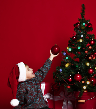 Cute little kid decorating Christmas tree with red beads