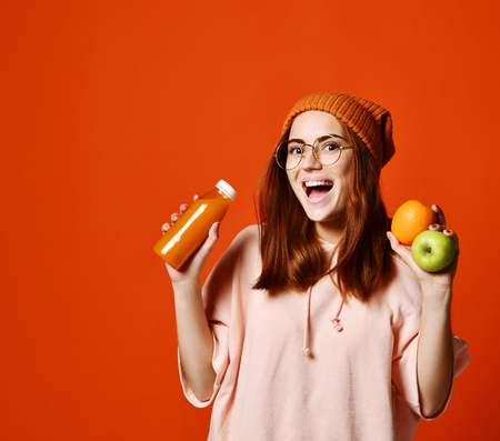 Portrait of a cute casual hipster girl in glasses with orange juice from bottle and apple and orange fruits and happy looking at camera isolated over orange background. Healthy lifestyle