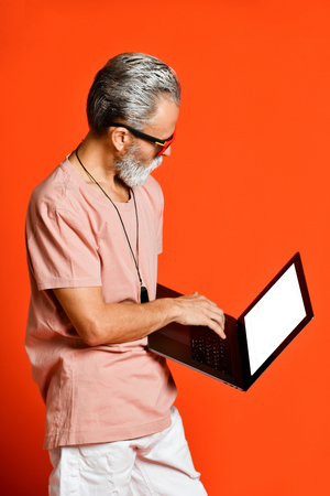 Happy portrait of trendy pensioner enjoying the use of new laptop. Youthful and stylish man in the sixties, concepts about lifestyle, seniors and business 写真素材