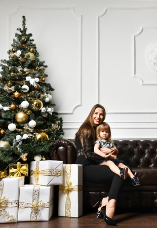 Mother with her child daughter dressed black suit in beautiful fashion celebrating near Christmas tree Stock Photo