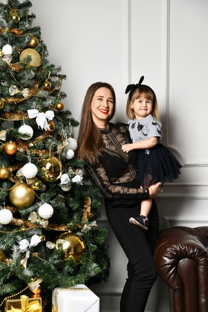 Mother with her child daughter dressed black suit in beautiful fashion celebrating near Christmas tree Banco de Imagens