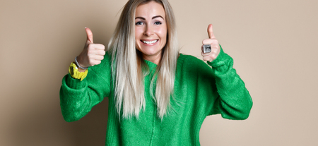 Portrait Of Smiling happy blonde woman pulling hands towards camera with thumbs up and smiling cheering and supportive against beige Background Banco de Imagens