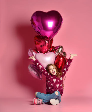 A little 7 year old girl is sitting on the floor holding a bunch of pink heart-shaped balloons. Celebrates birthday and Valentine's Day. Hangout. Birthday party.