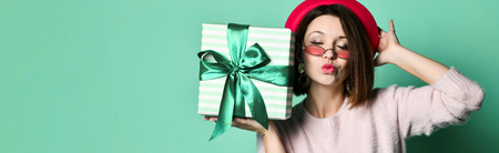 Photo of beautiful woman in felt hat holding present gift box and sending a kiss, isolated over blue background