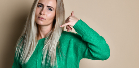 Woman in green sweater doing phone gesture like says: call me back with hand and fingers like talking on the telephone isolated on beige background. Communicating, people emotions, lifestyle Stock fotó