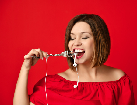 Attractive girl in red dress holding a fork in hands. on the headphone plug. prepared to eat. Music saturation