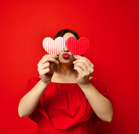adorable girl with valentine's day heart showing love kiss fun affection portrait on red background