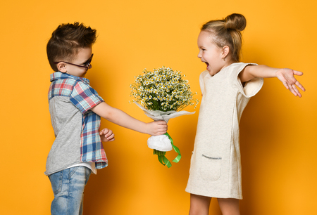 A little boy gives a bouquet of daisies to his girlfriend a girl. girl is happy to present and spread her arms wide to hug him. Concept of friendship, quarrel, date Фото со стока