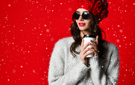 winter, people, happiness, drink and fast food concept - woman in hat with takeaway tea or coffee cup Stock Photo