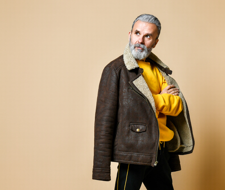 Portrait of elder stylish rich man with a beard and mustache in a leather winter coat, looking away the camera and He crossed his arms, the studio on a beige background copy space