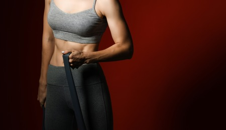 Cropped photo of muscular woman exercising with resistance band . Female perform fitness exercises. Low key red. Strength and motivation