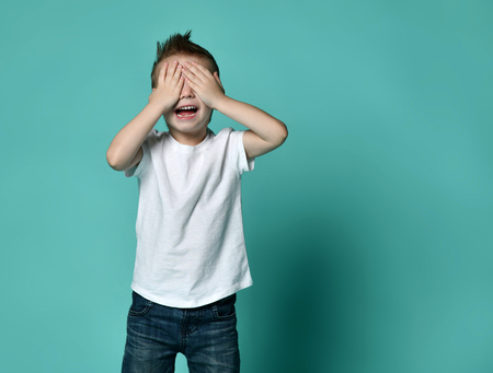 Young happy boy with brown hair screaming and covering eyes with hands isolated over light background