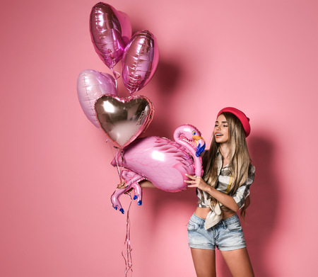 Glamor young slim girl in shorts and a hat holds bunch of balloons and one in the form of a flamingo. Fun party, hen party. birthday.