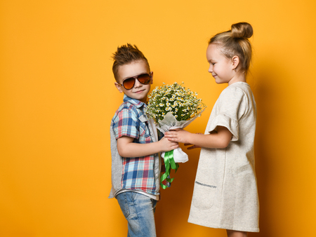 Little cute stylish boy gives a bouquet of daisies to his girlfriend blonde girl. romantic photo of a couple. A date or birthday gift