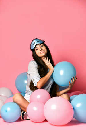 Portrait of trendy cheerful young woman having many color air balloons looking up enjoying ballons isolated on pink background. Celebration and party. Having fun