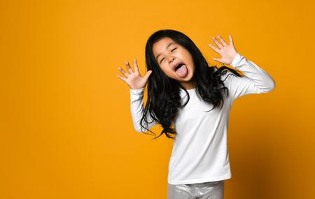 Divertida linda niña asiática muestra la lengua sobre fondo de pared amarilla