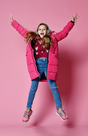 Young fashion child girl jumping over pink background, she dressed in short violet down jacket and jeans. fashion kids 스톡 콘텐츠