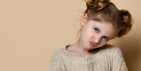 Naughty little girl in knitted huge sweater pouted her lips with resentment over the nude background