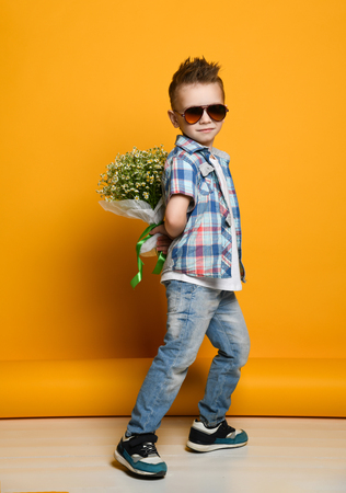 Cute little boy holding a bouquet of flowers. daisies. Mothers Day. International Womens Day. Portrait of a happy little boy on a yellow background. Spring. Standard-Bild