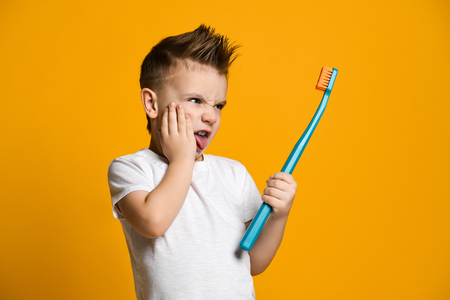 little boy in a white T-shirt holds his hand on his cheek - he has a toothache. He hold a huge toothbrush. He does not want to treat his teeth and does not want to brush his teeth. Dental problems Reklamní fotografie