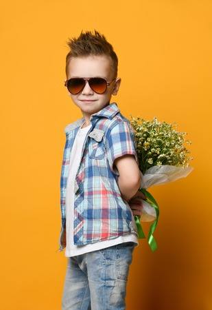 Cute little boy holding a bouquet of flowers. daisies. Mothers Day. International Womens Day. Portrait of a happy little boy on a yellow background. Spring. Stock Photo