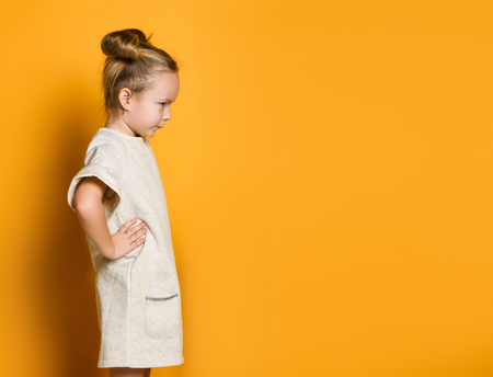 little cute girl in a light dress looks away angrily, her arms are in sides. On yellow background, sign and gesture concept, copy space Stockfoto