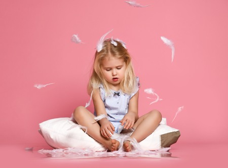 Funny small child with light hair, sitting on white pillow, feeling joy while catching feathers, having fun. Cute blue eyed girl wanting to sleep, playing in bed. Childhood concept