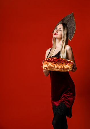 Young attractive woman in kokoshnik cap and sexy dress happy hold bite sweet berry homemade pie tasty bun and looking toward the empty space on red background Stock Photo