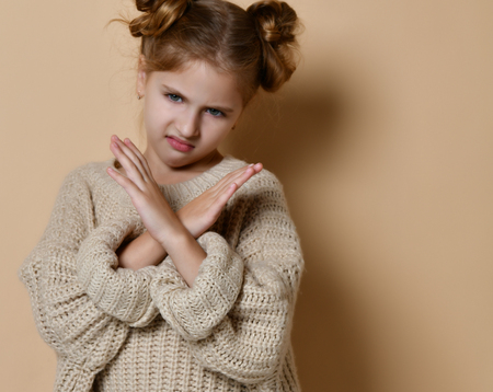 Portrait of serious, unhappy kid girl holding two arms crossed, gesturing no sign, looking away camera, isolated on beige background