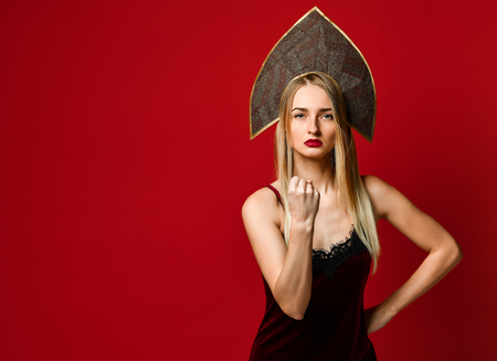 Angry beautiful young woman in kokoshnik hat shows fist at camera, threats someone dressed in velvet dress, isolated over red background, argues indoor Stock Photo