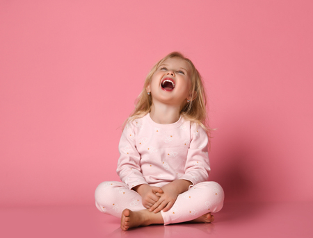Cheerful Little cute girl in pajamas sits on the floor having fun on pink background. girl laughs fascinated and looks up Reklamní fotografie