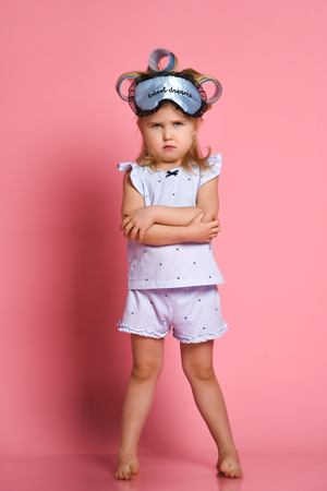 Dissatisfied little girl in pajamas and a sleep mask, she folded her arms in a pose on her chest and frowned at the camera Stockfoto
