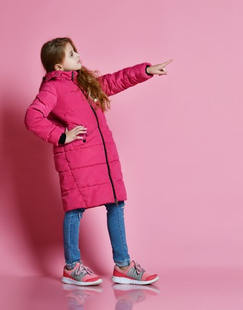 Full-length portrait of a little fashionable girl in a warm pink down jacket and jeans. She stands sideways and points in the direction of free space, on a pink background.