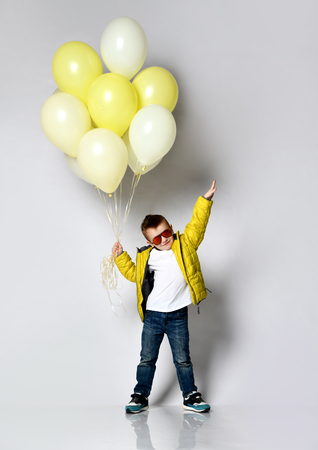 Boy schoolboy in a stylish jacket and hood holds a batch of balloons on white.