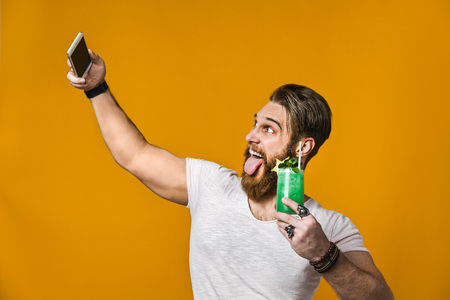 attractive bearded young man with a cocktail making selfie photo on a mobile phone for social networks