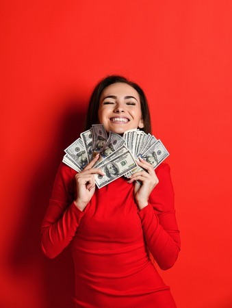 Young thinking pretty woman in red dress presses to herself a bunch of money banknotes, squinting from pleasure, isolated on red background