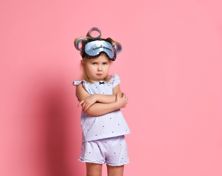 Dissatisfied little girl in pajamas and a sleep mask, she folded her arms in a pose on her chest and frowned at the camera Foto de archivo