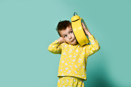 Cute little boy with alarm clock,isolated on blue. Funny kid yawning pointing at alarm clock at morning. Excited boy overslept before school. People, school, time and lifestyle concept