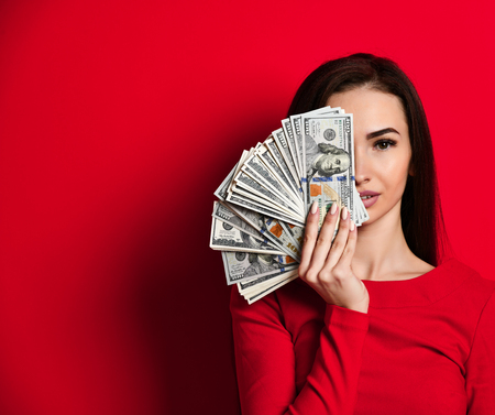 Portrait of a cute, tender, attractive, gorgeous girl in a red dress, covering half of her face with a fan of  100, isolated over a bright red background