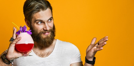 Attractive, stunning and cheerful bearded young guy smiles and holds a multicolored cocktail with a straw. A man looks and shows free space for your advertising. On a yellow background.
