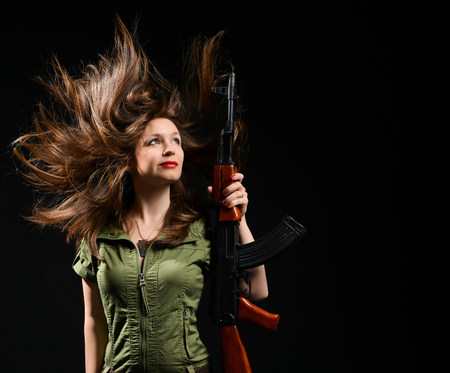young brunette girl in a green khaki dress holding a gun on a black studio background. 免版税图像