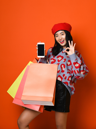 Young Asian girl in stylish beret with colorful pockets shows on the screen of the tablet. Online shopping