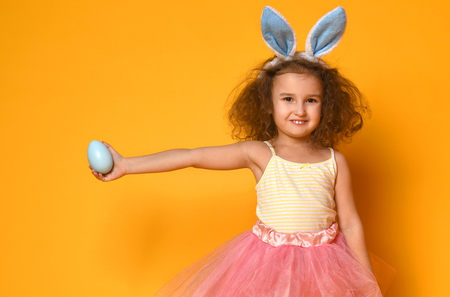 Cute little child girl wearing bunny ears on Easter day. Girl holding egg on yellow background
